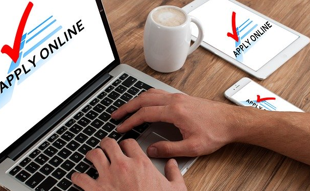 Bildbeschreibung: Auf dem Foto ist ein Laptop zu sehen und 2 Hände, die gerade einen Widerspruch auf der Tastatur tippen. Rechts neben dem Laptop ist noch eine Kaffeetasse sowie ein Tablet und ein Handy zu sehen. Ende der Bildbeschreibung.