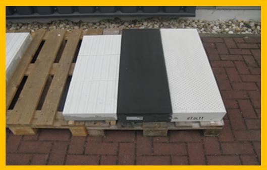 """Bild Bodenindikatoren: Auf einer Holzpalette liegen einige Bodenindikatoren – links: drei Bodenindikatoren mit Rippenprofil hintereinander - einem Leitstreifen andeutend; rechts: ein sogenanntes """"Bahnsteigsystem Gera"""", mit einer Tiefe von 60 cm die aufgeteilt ist in einen 30 cm breiten Anteil mit einer anthrazitfarbenen und fugenlosen Oberfläche und eine 30 cm breiten Bereich mit einer weißen Oberfläche die leicht genoppt ist."""