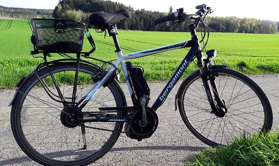 Foto: Auf dem Foto ist ein auf einem Weg abgestelltes E-Bike Pedelec zu sehen. Im Hintergrund ist eine grüne Wiese zu sehen, die zu einem Wald führt.