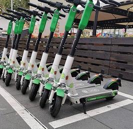 Foto: Auf dem Foto sind E-Scooter zu sehen, die in einer Reihe nebeneinander aufgestellt wurden.