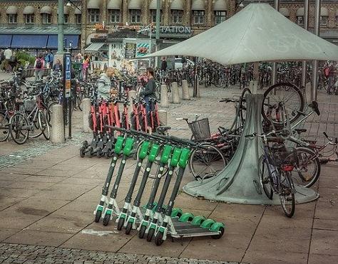 Bildbeschreibung: Vor einem großen Gebäude befindet sich eine Ausleihstation für Mobilitätshilfen mit Motorantrieb. Im Bildvordergrund befinden sich in einer Reihe aufgestellte E-Scooter. Dahinter befinden sich abgestellte E-Bikes.