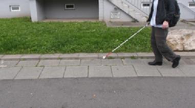 Foto: Auf dem Foto ist eine Frau zu shen, die mit einem Blindenlangstock auf einem Gehweg entlanggeht.