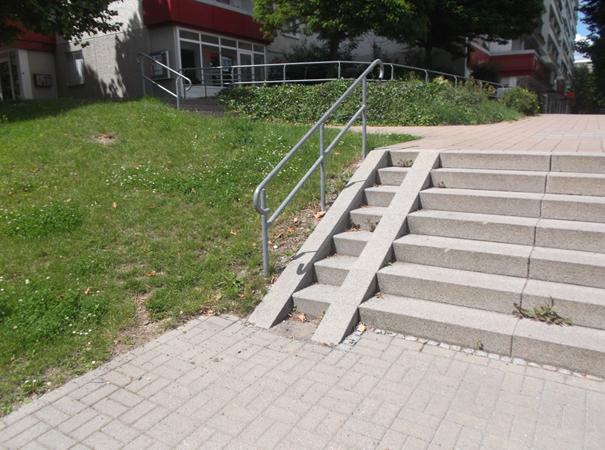Das Foto zeigt eine steile Rampe, die am Rand auf einer Treppe angelegt wurde. Die Treppe wird seitlich, neben der Rampe durch ein nicht kontrastierendes Geländer begrenzt. Die Rampe besteht, für die, rechten und linken Räderpaare eines Rollstuhls, aus jeweils ca. 10 cm breiten schiefen Ebenen, die sich vom Boden vor der untersten Stufe bis zur Trittfläche der obersten Stufe erstrecken. Der Zwischenraum zwischen beiden schiefen Ebenen ist mit Stufen versehen.