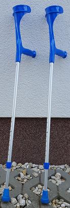 Foto: Auf dem Foto sind 2 Unterarmstützen abgebildet, die an einer weißen Hauswand lehnen