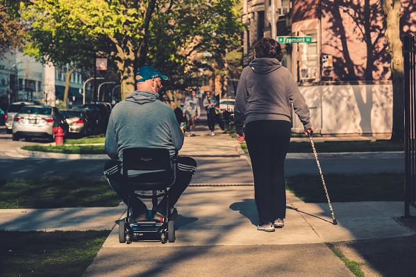 Foto 1 Ein Mann ist mit seinem Elektrorollstuhl unterwegs auf einem Gehweg und rechts neben ihm läuft eine Frau mit einem Gehstock in der rechten Hand