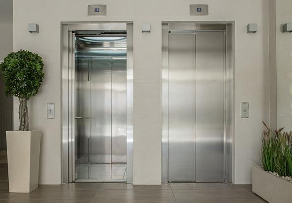 Bildbeschreibung: Auf dem Bild befinden sich zwei Personenaufzüge nebeneinander. Neben dem linken Aufzug befindet sich ein Buchsbaum in einem großen Pflanztopf, der auf dem Boden steht. Neben dem rechten Aufzug stehen auf dem Boden Gefäße mit Grünpflanzen. Ende der Bildbeschreibung.