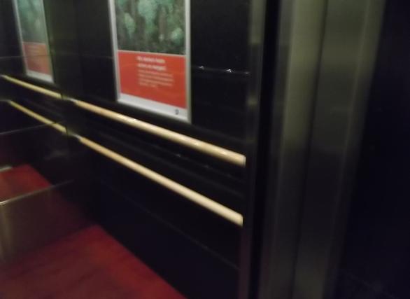 Bildbeschreibung: Das Bild zeigt einen Blick (von außen) auf die rechte Aufzugsinnenwand. Auf der dunkeln Aufzugswand befinden sich zwei übereinander angeordnete gelbe Handläufe. Darüber befindet ein Werbeplakat. Ende der Bildbeschreibung.