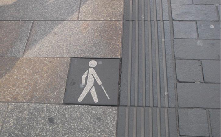 """Bildbeschreibung: Das Bild zeigt einen Blindenleitstreifen mit geringen visuellen Kontrast zum Gehwegbelag. An dessen linken Seite ist eine Gehwegplatte mit einen """"Stockmännchen"""" angeordnet. Ende der Bildbeschreibung."""