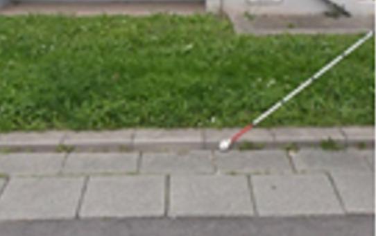 Bildbeschreibung: Das Bild zeigt einen Blindenlangstock der beim Pendeln an eine Rasenkante stößt. Ende der Bildbeschreibung.