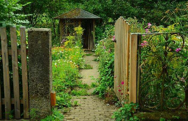 Bildbeschreibung: Das Foto gewährt den Blick in einen Bauerngarten. Das Gartentor aus Holz auf der rechten Bildseite ist geöffnet. In der Bildmitte führt ein Plattenweg, der zum Teil mit Pflanzen bewachsen ist, auf einen Gartenpavillon aus Holz mit einem Spitzdach zu. Rechts und links des Weges wachsen verschiedene Blumen in unterschiedlicher Höhe und bunten Blütenfarben, wie rosa und gelb. Ende der Bildbeschreibung.