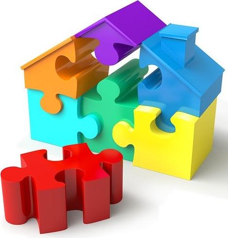 Bildbeschreibung: Das Bild zeigt ein Haus aus bunten 3 D Puzzleteilen, wobei ein rotes Teil, was im Dach des Hauses fehlt, im Bildvordergrund liegt. Ende der Bildbeschreibung.