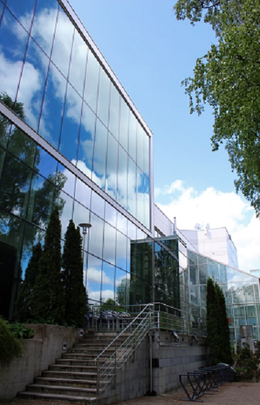 Bildbeschreibung: Links auf dem Bild befindet sich die Glasfassade eines Hochhauses, indem sich die Wolken und Bäume spiegeln. In der Bildmitte befindet sich eine am Gebäude angebrachte Treppe, die noch oben zum Eingang des Gebäudes führt. In der rechten oberen Ecke des Bildes ist die Krone eines Laubbaumes angedeutet. Ende der Bildbeschreibung.