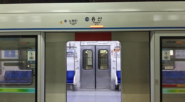 Bildbeschreibung: Das Bild 2 gewährt einen Blick durch die offene Tür eine U-Bahn ins Fahrzeuginnere. Dabei ist die Tür sich gerade im Begriff zu schließen, was durch das gelb aufleuchtende Türschließwarnsignal oberhalb der Tür in der Bildmitte dargestellt wird. Ende der Bildbeschreibung.