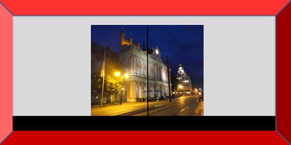 Bildbeschreibung: Das Bild 2 zeigt den Blick auf das nächtlich angeleuchtete Rostocker Rathaus durch eine Glastür ohne visuelle Kennzeichnung. Ende der Bildbeschreibung.
