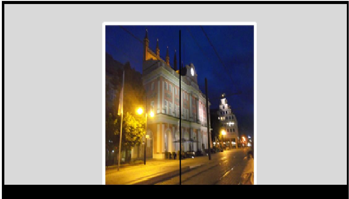 Bildbeschreibung: Blick durch eine Glastür zum nächtlich beleuchteten Rostocker Rathaus. Ende der Bildbeschreibung.