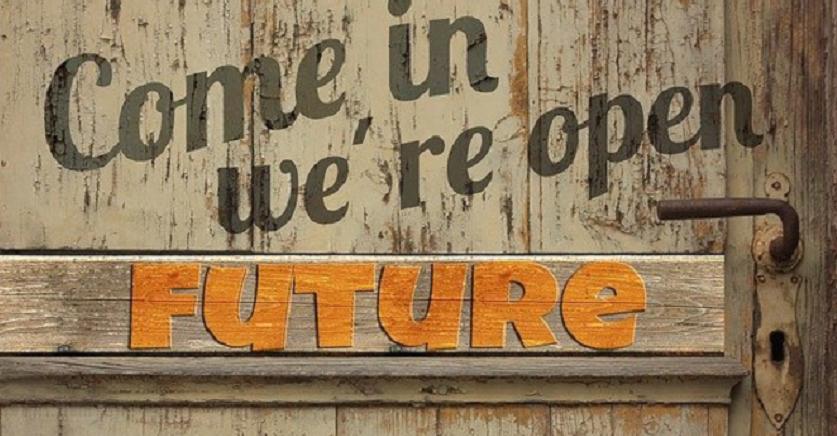 Bildbeschreibung: Das Foto zeigt eine den Ausschnitt einer alten hellbraunen Holztür. Links neben der Türklinke, die einen verrosteten Eindruck macht, befindet sich in orangefarbenen Großbuchstaben das englische Wort Future. Oberhalb der Türklinke steht in dunkelbrauner Farbe der englische Schriftzug Come in, we are open. Ende der Beschreibung.