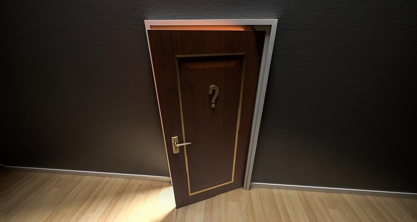 Bildbeschreibung: Bild 1 zeigt eine dunkelbraune, geöffnete, mit einem messingfarbenen Fragezeichen versehene Zimmertüre am Ende eines leeren Raumes mit hellem Parketboden und schwarzen Wänden. Ende der Bildbeschreibung.