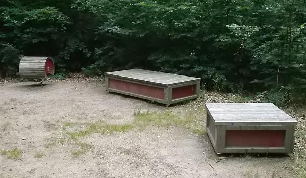 Bildbeschreibung: Auf Bild 7 sind zwei quaderförmige und eine runde Sitzgelegenheit, je aus mehreren Holzbrettern bestehend, zu sehen, unter denen sich eine Feder befindet. Damit sind die Sitzgelegenheiten im Waldboden verankert. Ende der Bildbeschreibung