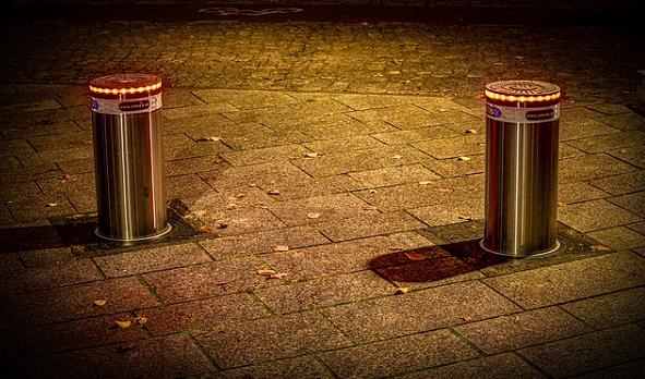 Bildbeschreibung: Das Bild 1 zeigt 2 im Abstand nebeneinander stehende beleuchtete Poller auf einem Gehweg bei Nacht. Ende der Bildbeschreibung.