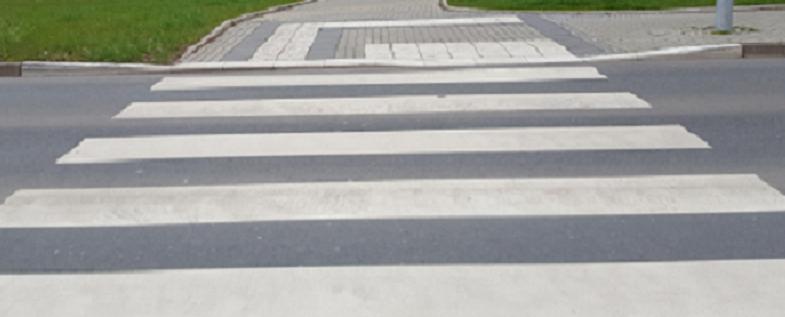 Bildbeschreibung: Das Bild 8 zeigt einen Fußgängerüberweg mit differenzierter Bordhöhe. Im hinteren Drittel des Bildes ist auf der rechten Seite eine abgesenkte Bordsteinkante zu sehen, die für Rollator - und Rollstuhlnutzer vorgesehen ist und links daneben befindet sich das erhöhte Bord mit Blindenleitsystem für die Fußgänger. Ende der Beschreibung.