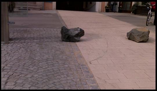 Bildbeschreibung: Das Bild 13 zeigt zwei Findlinge, die quer über die nutzbare Gehwegbreite angeordnet wurden. Ende der Bildbeschreibung.