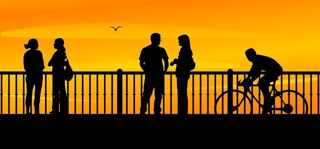 Bildbeschreibung: Bild 4 zeigt 4 Menschen als Silhouette im Sonnenuntergang auf einer Brücke, die am Geländer stehen. Von hinten nähert sich ihnen ein Fahrradfahrer. Ende der Bildbeschreibung.
