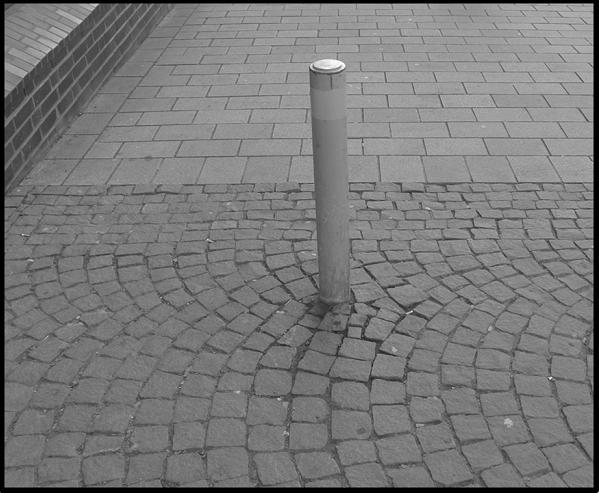 Bildbeschreibung: Bild 2 zeigt in der Mitte eines, mit grauen Granitsteinen, gepflasterten Gehweges einen grauen Poller / Sperrpfosten. Ende der Beschreibung.