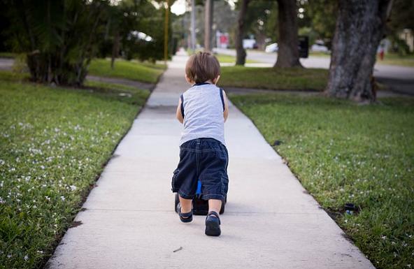 Bildbeschreibung: Bild 1 zeigt einen kleinen Jungen von etwa 2 Jahren, der auf einem Gehweg vom Betrachter wegläuft. Der Betonweg ist recht und links von Rasen umgeben, auf dem Bäume und Sträucher zu sehen. Ende der Beschreibung.