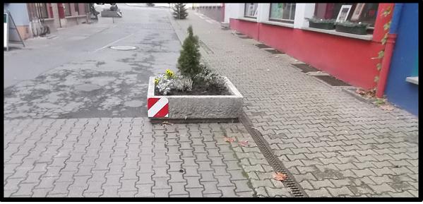 Bildbeschreibung: Das Bild 10 zeigt einen rechteckigen Pflanzkübel aus Beton in der Mitte eines verkehrsberuhigten Bereichs stehen. An seiner linken Seite ist er mit einem rot-weiß-schraffierten Rechteck gekennzeichnet. Ende der Bildbeschreibung.