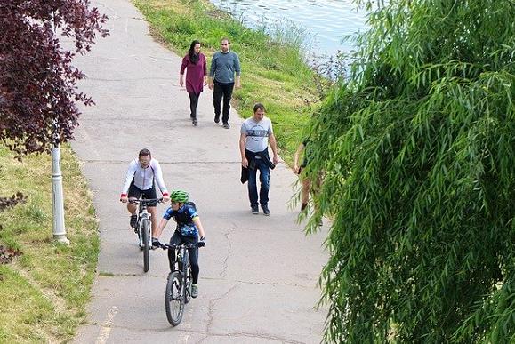 Bildbeschreibung: Bild 1 zeigt einen Fußweg, auf dem sich rechts drei Fußgänger und links vor Ihnen 2 Radfahrer befinden. Der Fußweg grenzt rechts an ein Gewässer. Ende der Beschreibung.