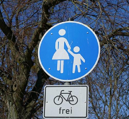 """Bildbeschreibung: Bild 3 zeigt ein rundes Verkehrszeichen mit weiß auf blauen Hintergrund abgebildeten Frau (links) mit Kind (rechts). Unterhalb diesem ist zusätzlich ein weißes rechteckiges Schild mit schwarzem Rahmen angeordnet. In dessen Mitte ist ein schwarzes Fahrrad abgebildet, worunter das Wörtchen """"frei"""" in schwarzen Kleinbuchstaben steht. Ende der Bildbeschreibung."""
