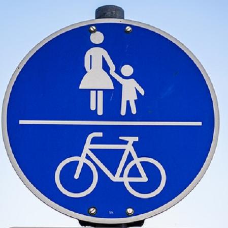 Bildbeschreibung: Auf Bild 6 sind auf dem runden Verkehrszeichen weiß auf blau, oberhalb eine Frau mit einem Kind (entsprechend Zeichen 239) und unterhalb ein Fahrrad abgebildet. Beide Symbole sind durch einen waagerecht verlaufenden Strich getrennt. Ende der Bildbeschreibung.