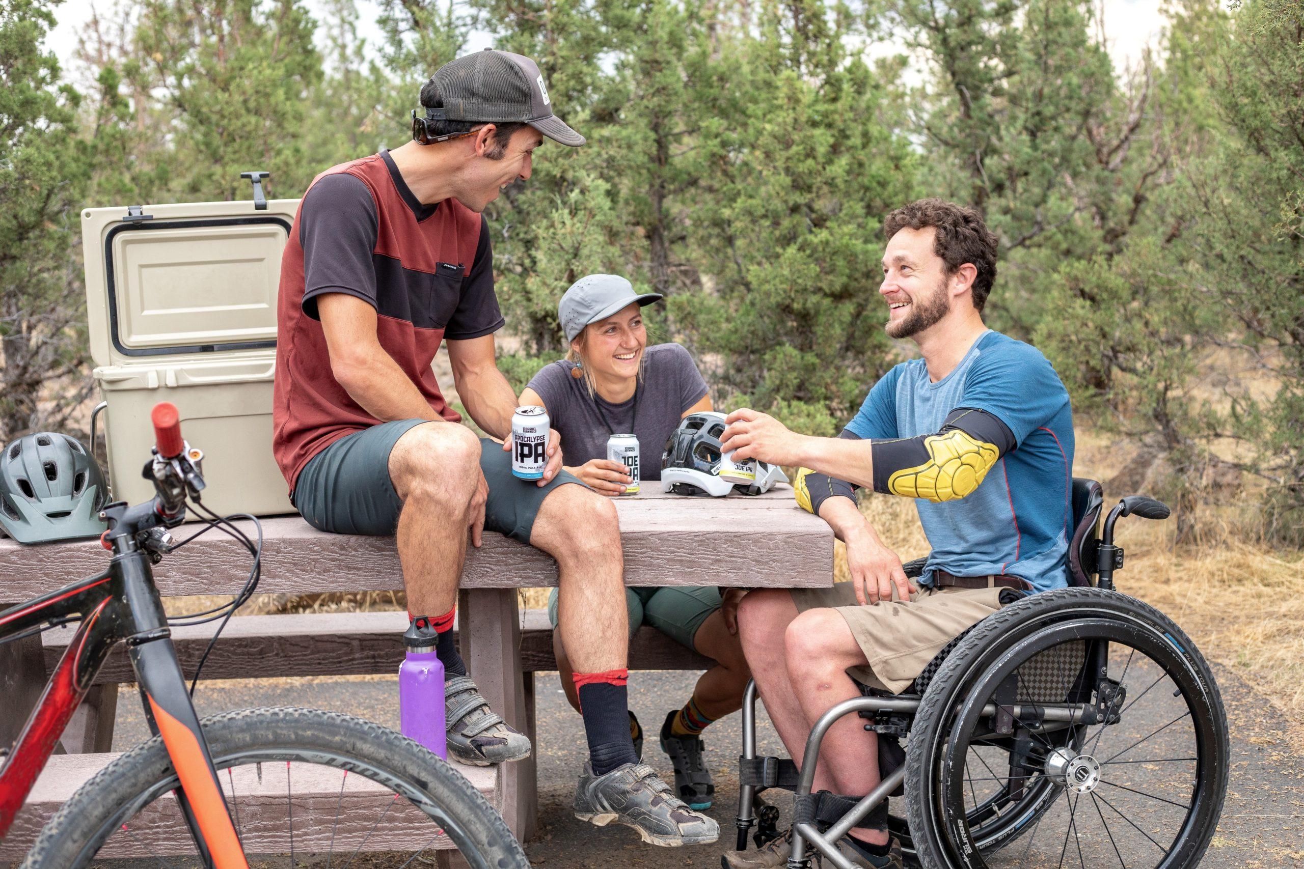 Bildbeschreibung: Bild 1 zeigt 2 Personen mit Fahrrad und ein Rollstuhlfahrer an einen Verweilplatz im Park. Ende der Beschreibung.