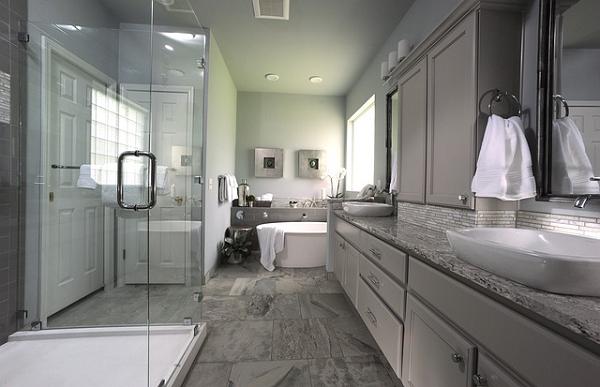 Bild 1 zeigt den Blick in ein Badezimmer. Rechts 2 Wascbecken, links 1 Dusche. Hinter der Dusche die Tür. Hinten mittig die Badewanne. Ende der Beschreibung.