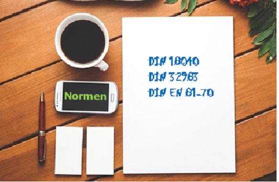 Bildbeschreibung: Das Bild zeigt die Daufsicht auf einen Tisch. Darauf befindet sich links eine Kaffeetasse und ein Handy und rechts daneben ein Block auf dem 3 Normen aufgeschrieben sind. Ende der Beschreibung.