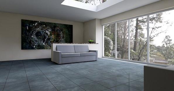 Bildbeschreibung: Das Bild zeigt einen Wohnraum mit einem Dachfenster und einer Glasfassade rechts. Auf den grauen glänzenden Fließen befindet sich in der Mitte eine graue Couch. Dahinter hängt ein Bild an der Wand. Ende der Beschreibung.