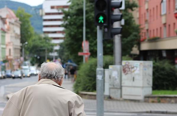 Bildbeschreibung: Das Bild zeigt einen älteren Mann, wie er gerade bei grün die Straße überquert. Ende der Beschreibung.