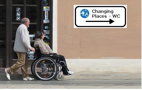 Das Bild 1 zeigt ein Mann der eine Frau im Rollstuhl schiebt vor einer hauswand mit dem Hinweis auf ein Changing Places WC.