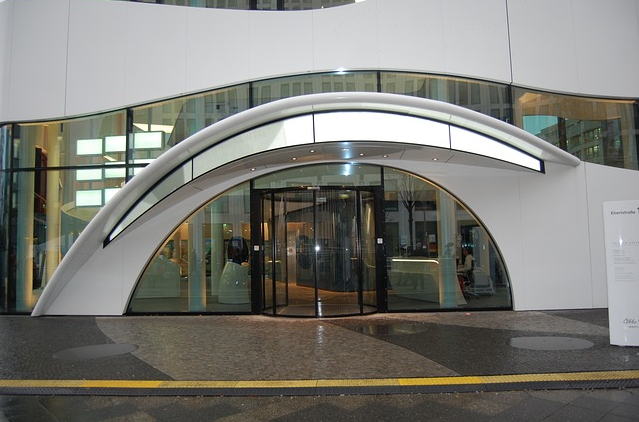 Bildbeschreibung: Bild 1 zeigt den Blick auf ein öffentliches Gebäude mit einer Glasdrehtür am Eingang. Ende der Beschreibung.