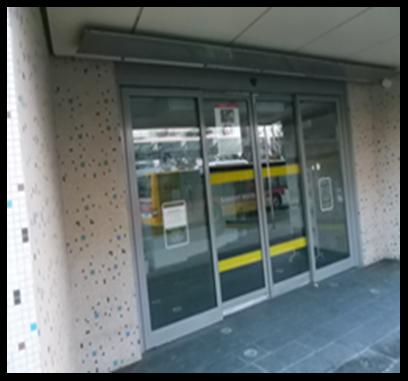 Bildbeschreibung: Das Bild 6 zeigt eine Glasschiebetür im Eingangsbereich eines Verwaltungsgebäudes. Ende der Beschreibung.