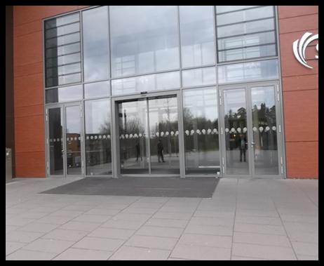 Bildbeschreibung: Das Bild 7 zeigt eine große Glasfassade mit integrierter Glasschiebetür im Eingangsbereich eines Krankenhauses. Ende der Bildbeschreibung.