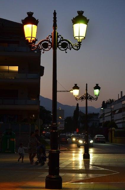 Das Bild 1 zeigt eine beleuchtete Straße, links Personen vor einem Gebäude, in der Bildmitte eine Straßenlaterne und im Hintergrund fahrende Autos.